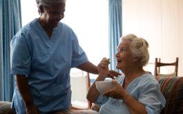 senior eating with caregiver