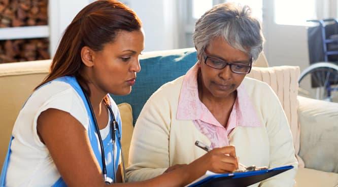 senior woman and caregiver looking at a pad