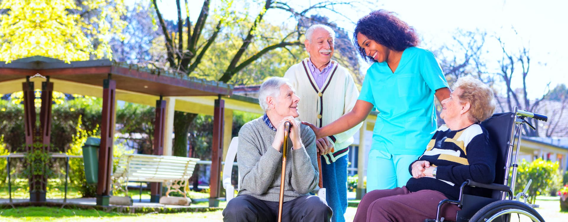 group of senior patients and a caregiver smiling
